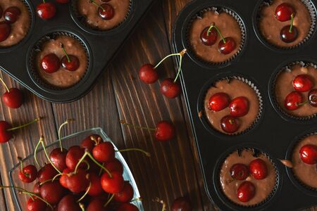 Baking chocolate muffins. Raw vegan banana cherry muffins with fresh berries on brown wooden background. Top view. Summer food Archivio Fotografico