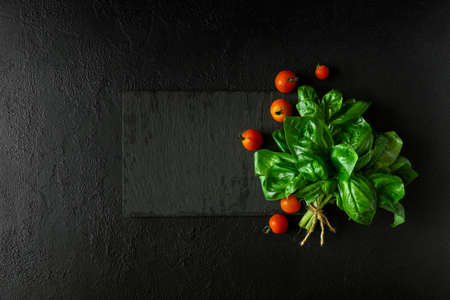 Fresh green basil and cherry tomatoes on slate plate and dark concrete background. Top view. Flat lay