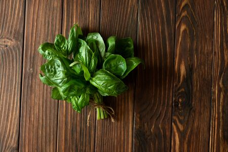 Fresh green basil on brown rustic wooden background. Top view. Flat lay