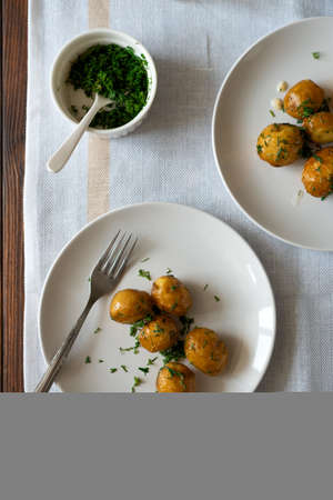 Oven-baked potatoes with garlic and herbs on plate. Summer food eating. Top view