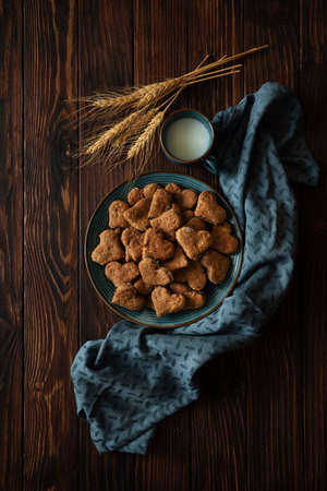 Top view on homemade wholegrain cookies with oatmeal, raisin, nuts, seeds and milk on brown rustic wooden background. Healthy eating concept. Copy space