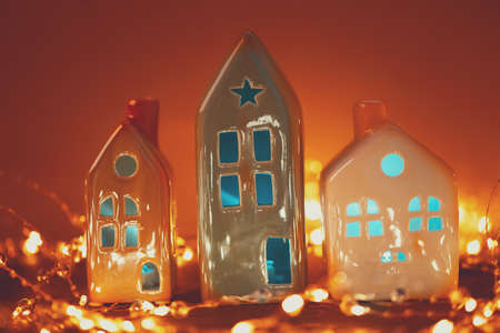 Christmas candle houses against bokeh lights background. New Year or Christmas celebration concept