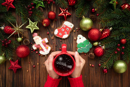 Woman holding hot Christmas tea with Santas sleigh and deers reflection against decorations on wooden table. Top view. New Year