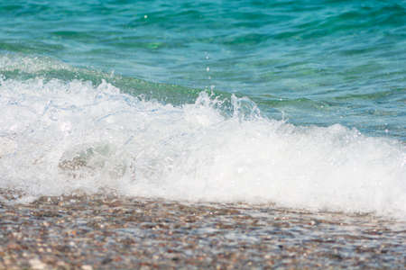 Soft turquoise sea wave on pebble beach. Nature background Stock fotó
