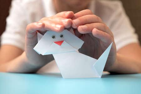 Child hands holding white paper cat on blue background. Animal shelter concept Stock fotó