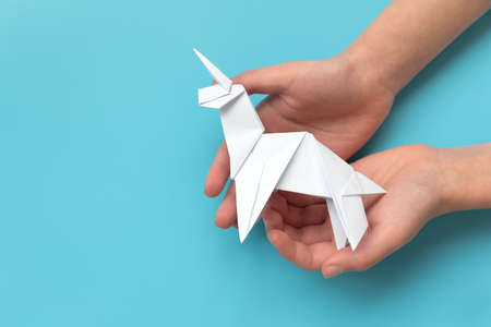 Child hands holding white paper unicorn on blue background Stock fotó