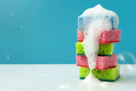 Stack of kitchen cleaning sponges with soap bubbles on blue background. Front view