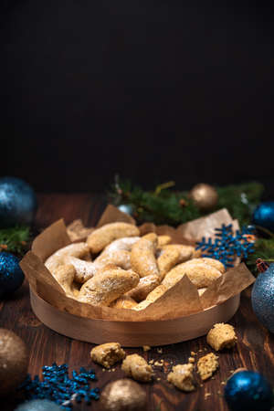 Homemade Christmas nuts cookies vanilla crescent with sugar powder in Christmas decorations. New Year and Christmas celebration concept. Copy space. Soft focus. Flying sugar powder Stock fotó