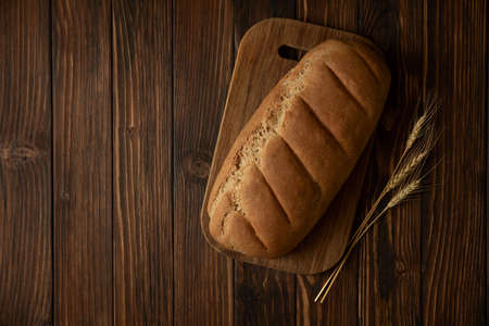 Homemade rye bread on wooden cutting board. Top view Stock fotó