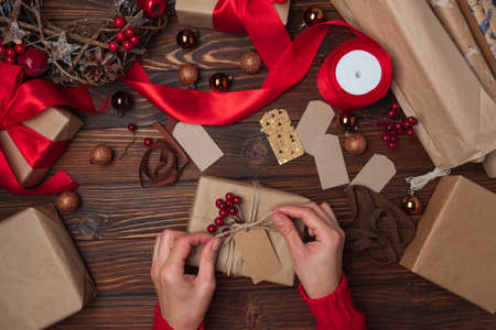 Female hands wrapping gift box on brown wooden table. Top view. New Year or Christmas celebration concept. Stock fotó