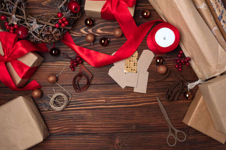 Wrapping gift box on brown wooden table. Top view. New Year or Christmas celebration concept. Copy space