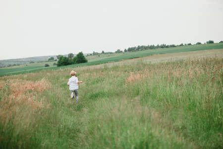 Happy boy running on green grass against sky. Soft focus. Summer activities Stock fotó