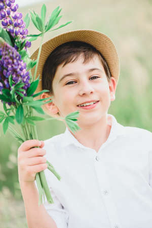 Portrait of happy smiling boy holding bouquet of lupines on green grass against sky. Soft focus. Summer activities