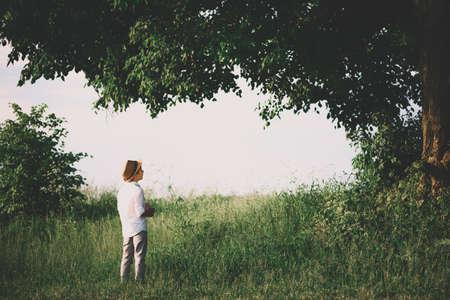Little boy staying under big linden tree. Soft focus