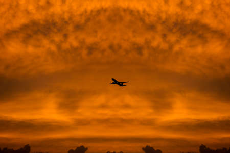Commercial airplane flying through clouds in dramatic sunset light. Travel concept Stock fotó