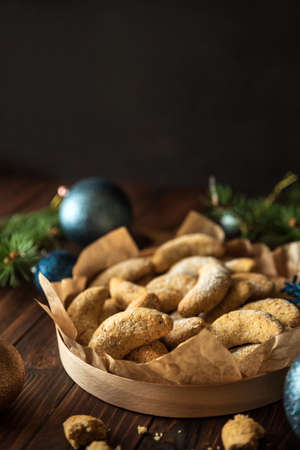 Homemade Christmas nuts cookies vanilla crescent with sugar powder in Christmas decorations. New Year and Christmas celebration concept. Copy space. Soft focus. Front view