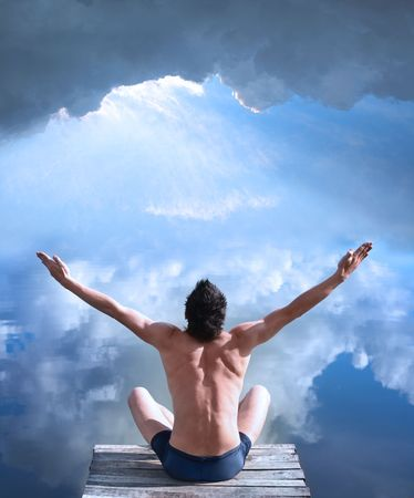 A man is sitting with his hands raised in the air at the water where the blue sky is mirrored photo