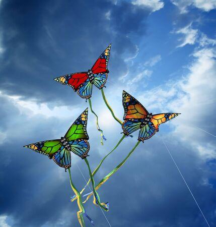 papalote: Tres coloridos cometas en el cielo nublado