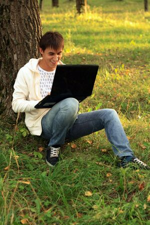 tree works: Student sitting by tree works with laptop Stock Photo