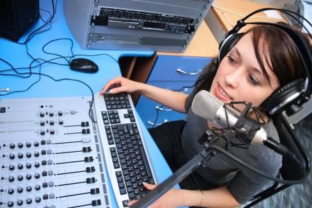 radio dj: A radio DJ announces news in a studio