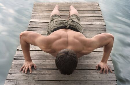 muscle tension tense: A man makes pushing up on the old wooden brige