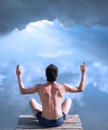 A man is sitting at the water where the blue sky is mirrored photo