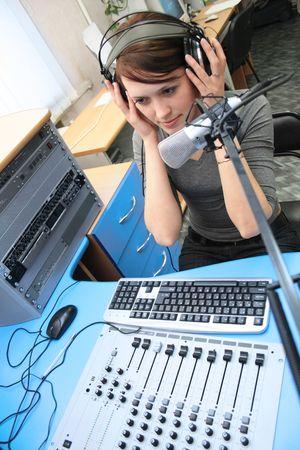 A radio DJ with headphones in the broadcasting studio photo