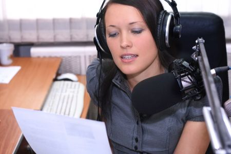 A radio DJ reads news in the broadcasting studio