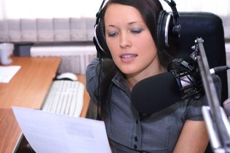 Una radio DJ legge la diffusione di notizie in studio