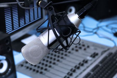 radio microphone: A mic in front of the control panel in broadcasting studio Stock Photo