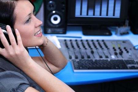 radio station: A radio DJ with headphones in the broadcasting studio