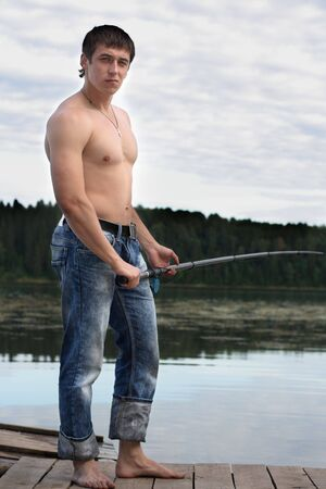 shirtless man: Young shirtless man holds rod Stock Photo