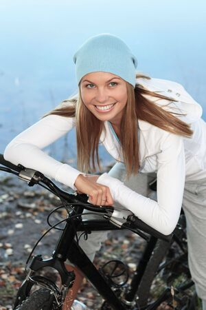 Young pretty woman sits on the bicycle against the still blue water