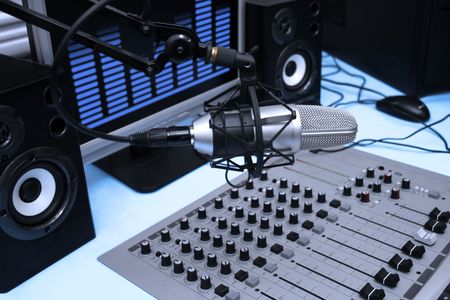 radio station: A mic in front of the control panel and screen in broadcasting studio Stock Photo