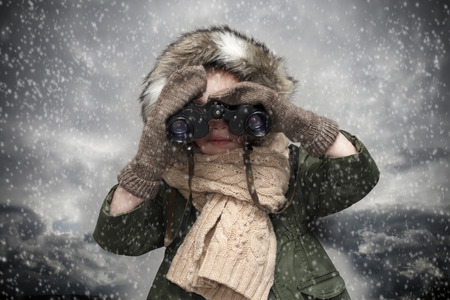 unexplored: Child is looking through the binoculars at snowy and cloudy background