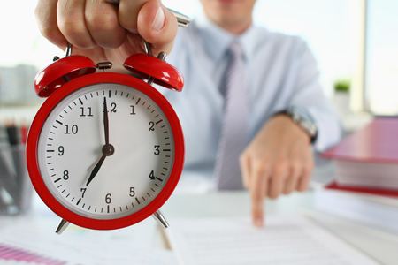 Male hand on the alarm clock a red color stands in the office on the table showing seven oclock in the morning or evening AM PM