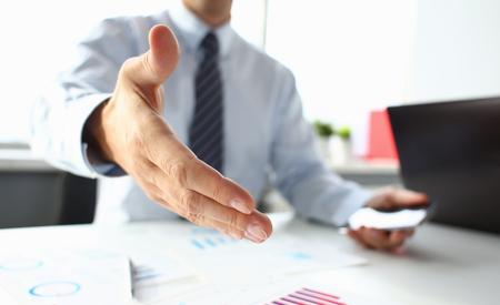 L'uomo in giacca e cravatta dà la mano come ciao in primo piano dell'ufficio.