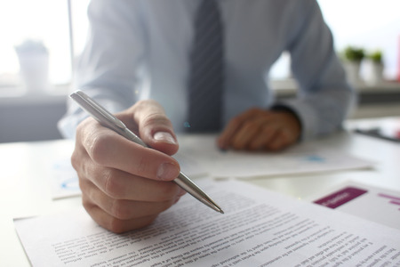 Hand of businessman in suit filling and signing with silver pen partnership agreement form clipped to pad closeup. Management training course, some important document, team leader ambition concept