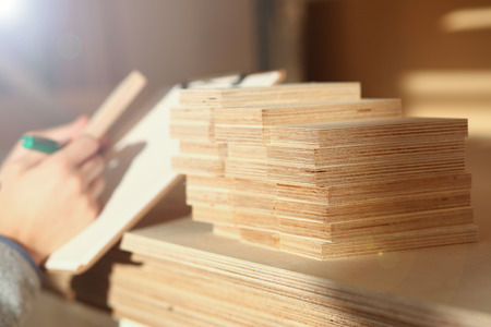 Wooden bars lying in a row closeup with manual worker in background. DIY job, inspiration, improvement, fix shop, powersaw bench, joinery startup, workplace idea, career, ruler, industrial education