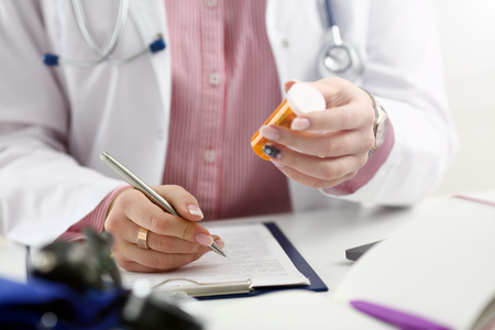 Female medicine doctor hand hold jar of pills and write prescription to patient at worktable. Panacea and life save, prescribing treatment, legal drug store concept. Empty form ready to be used