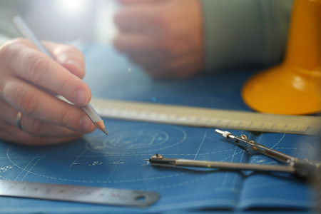 Male hand holding pencil in hand. Engineering blueprint design for buildings of blue architecture tools to achieve a human activity