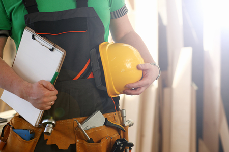 Handyman with hands on waist and tool belt with construction tools against wood background. DIY tools and manual work concept