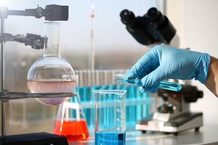 Un químico de sexo masculino sostiene un tubo de ensayo de vidrio en su mano desborda una solución líquida de permanganato de potasio realiza una reacción de análisis toma varias versiones de reactivos usando fabricación química