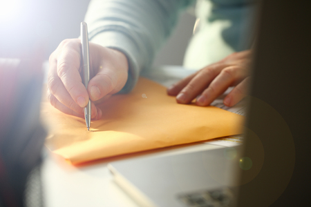 Male hand holding silver pen. Fill in address on yellow envelope of mail correspondence for application hiring concept Stock Photo
