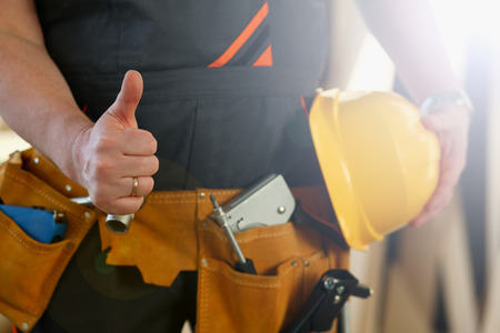 Hand of worker in yellow helmet show confirm sign with thumb up at arm portrait. Manual job DIY inspiration joinery startup idea fix shop hard hat industrial education profession career concept