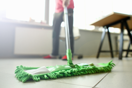 Green plastic mop cleaning laminated light dirty floor closeup