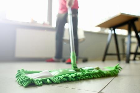 Primo piano sporco leggero laminato di pulizia della scopa di plastica verde del pavimento