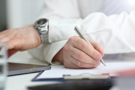 Male arm in suit and tie hold silver pen filling schedule in notepad at office workplace closeup. Legal law consult assistance gesture or finance investment advisor clerk job information gesture