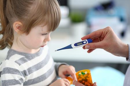 Female hand holding thermometer measuring sick little girl closeup Foto de archivo