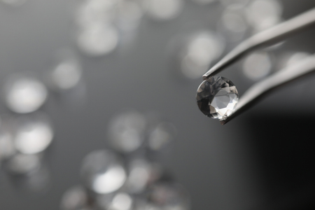 The jeweler holds a diamond in tweezers Stock Photo